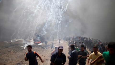 Palestinian demonstrators run from tear gas fired by Israeli troops